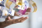 Hände werfen Geldscheine in die Luft
