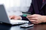 Hand hält Kreditkarte während OnlineBanking am PC